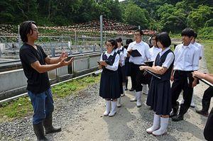 岡村場長(左)からサーモン養殖事業について説明を受ける生徒たち