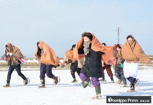 角巻姿で一斉に雪原に駆けだす「地吹雪体験ツアー」の参加者ら=20日午前