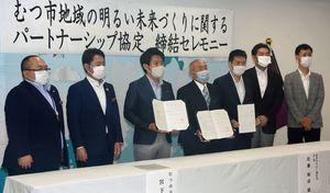 市と協定を結び、宮下市長(左から3人目)と記念撮影する佐藤会長(同4人目)ら