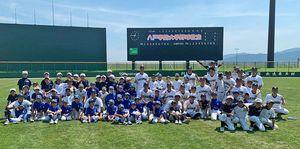 野球教室に参加した岩手県陸前高田市の子どもたちと記念撮影する八戸学院大硬式野球部員ら(同部提供)