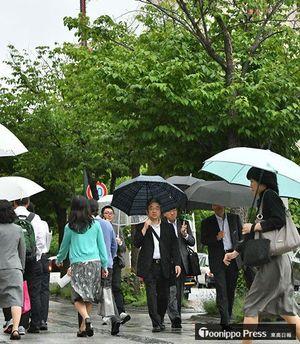 小雨が降りだし、歩道に傘の花が開いた青森市中心部=11日午後5時半、同市新町2丁目