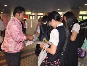 弘前青年会議所が開いた「城下町シンポジウム」でハーマン号事件を紹介するパンフレットを配る黒部さん(左)=2010年6月、弘前市民会館