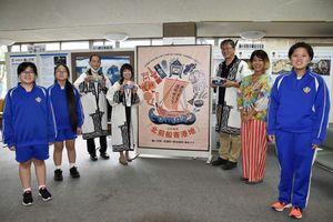 日本遺産3港PRイラストを前に、記念撮影する3町の担当者と野辺地中美術部員、豊川さん(右から2人目)