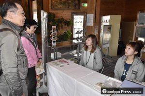 外国人観光客に鶴の舞橋までの行き方を説明する観光ガイドの岡さん(右)と工藤さん(右から2人目)
