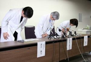 記者会見で謝罪する京大病院の宮本享病院長(中央)ら=19日午後、京都市
