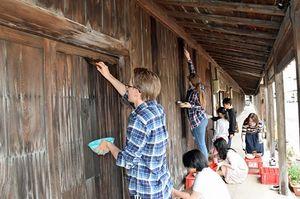 旧佐藤酒造のこみせの板塀に、柿渋を塗る参加者たち=黒石市元町