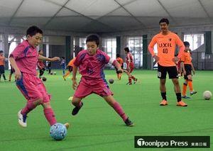 小笠原選手(右)のアドバイスを受け、ドリブル突破の練習をする子どもたち