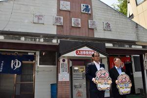 大湯の前でカウントダウンボードをお披露目する冨岡村長(左)と平井会長