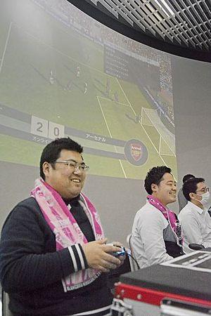 観客用にゲームを映し出した大画面を背に、サッカーゲームに興じる参加者=14日、青森市