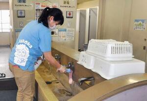 学校施設の消毒作業をする教諭=2日午後、北九州市