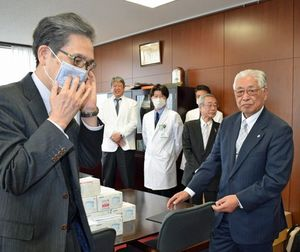 吉田代表理事(右)から贈られたマスクを着ける福田病院長(左)