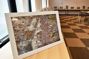 写真展の準備が進む会場。40年前の街並みを写した航空写真に、地名や学校名などが記されている