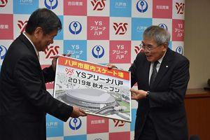 「YSアリーナ八戸」のパネルを小林市長(左)に贈る吉田社長