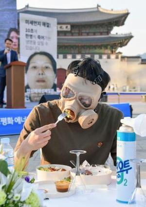 「PM2・5」対策を訴えるイベントで、マスクを着けて食事をする人=14日、ソウル(共同)
