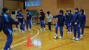 アイマスクをしてボールを蹴り、コーンに当てるゲームをする生徒ら