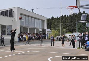 新校舎前のバスケットコートでシュートを放つ関根中生。後方が「やすらぎホール」