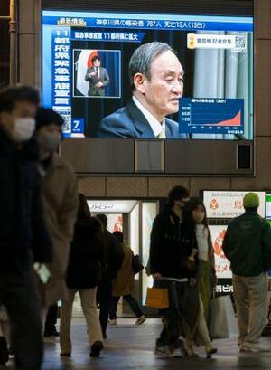 記者会見する菅首相を映す大阪・道頓堀の大型モニターと、マスク姿で行き交う人たち=13日午後7時11分