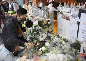死亡した男子大学生が転落した現場近くで花を手向ける人たち=8日、香港・新界地区(共同)