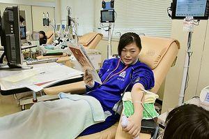 献血を受ける青森北高校吹奏楽部の坂本さん=3月下旬、青森市の県赤十字血液センター青森献血ルーム