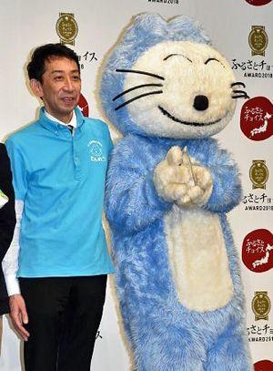 優秀賞の記念品を手にした「11ぴきのねこ」と記念撮影する沼澤課長=21日、東京・南青山