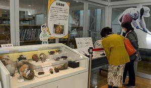 3遺跡の出土品が展示されたコーナーでは来場者が熱心に見入った