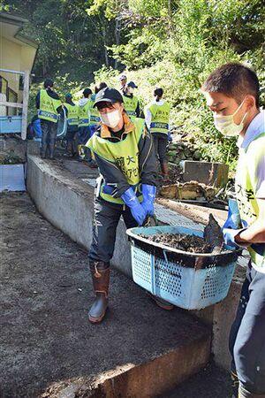 台風19号被害があった岩手県野田村玉川地区で、民家を覆った泥などを運び出す弘大生ら=20日午前
