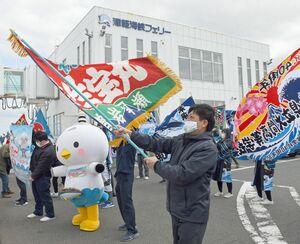 大漁旗を振り大函丸の乗客を歓迎する菊池組長(手前)ら
