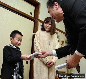 須藤会長(右)から記念品を受け取る千葉章誠ちゃん。中央は母いずみさん
