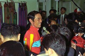 悲願のダービージョッキーとなり、大勢の報道陣に囲まれる柴田=1993年5月、東京競馬場(JRA提供)