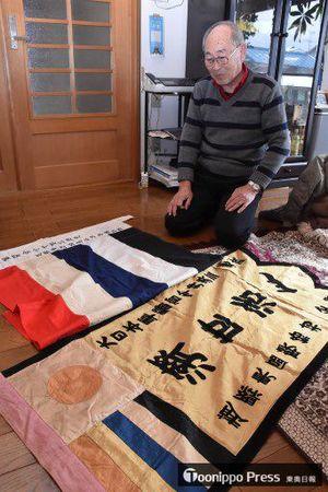 父・英三さんに贈られた旗を見つめる英輝さん。英三さんが生前、戦時中の話をすることはほとんどなかったという=5日、弘前市