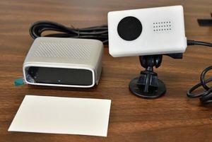 名刺(左手前)とほぼ同じ大きさの小型AIカメラ(左)。右はリアルタイムに運転手の警告情報を伝えるレンタルタイプ
