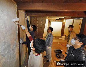 土蔵の壁を漆喰で丁寧に塗っていくボランティアの参加者