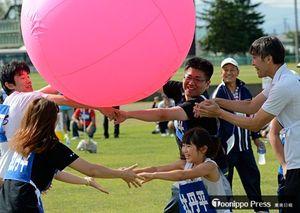 参加者が手をつないで大きなボールを目的地まで運ぶ「大玉運び」で、笑顔を見せる市民ら