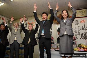 無投票で再選を決め万歳三唱する宮下氏(中)。右は妻悠美さん=27日午後5時51分、むつ市緑町の選挙事務所