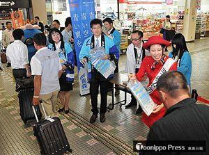 大阪からの到着客に記念品を渡すミスりんごや全日空関係者=1日午前10時55分、青森空港