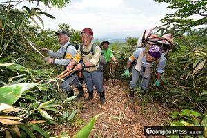 ハサミを使って登山道のササなどを刈り払いする会員=19日、高田大岳