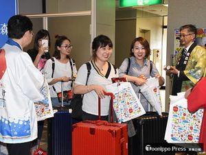 青森空港に到着し、青森県関係者から歓迎を受ける乗客=16日午後4時ごろ