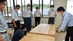 伐採した木材で試作したテーブルを確認する出席者