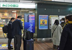運行見合わせや遅延など、新幹線の運行状況を確認する利用客ら=20日午後7時23分ごろ、八戸駅