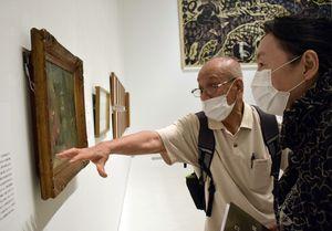 志功の隣の家に住んでいた当時を振り返りながら、寄贈した油絵を鑑賞する二村さん(左)