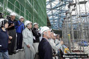 スタンド部分からスケート場の鉄骨などを見学する参加者