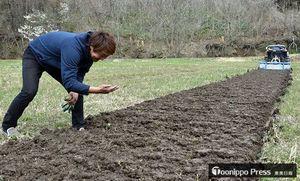自然栽培に取り組む田で、掘り起こされた土の感触を確かめる佐藤代表(左)。「良い土だ」と笑顔がこぼれる=4月下旬、黒石市高舘