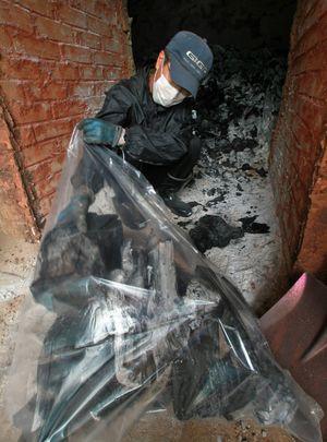 炭焼き窯からリンゴの木の炭を取り出す長尾さん