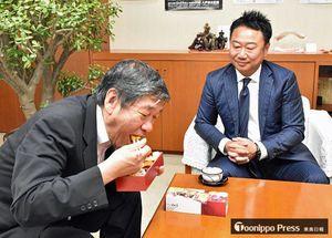 ウニをふんだんに使った弁当を試食する小林市長(左)と吉田社長