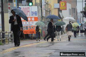 梅雨前線の影響で時折強い雨が降る中、通勤・通学を急ぐ傘の列がみられた=27日午前7時45分ごろ、青森市古川2丁目