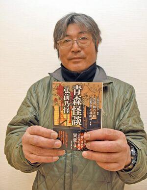 「弘前乃怪」が初めて出版した怪談本を手にする代表の鉄爺さん