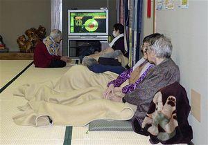 避難所となった八戸市白銀公民館でテレビのニュースを見守る住民=12日午後5時10分