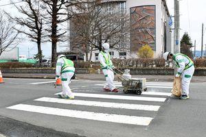 横断歩道の白線を引き直す作業員=5日午前9時10分ごろ、青森市花園