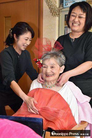 化粧をしアクセサリーを着けた姿を鏡で見て、思わず笑顔になる施設利用者の女性