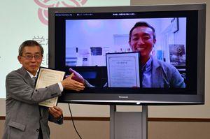 協定締結後、記念撮影に応じる加藤理事長と辻代表(右画面)